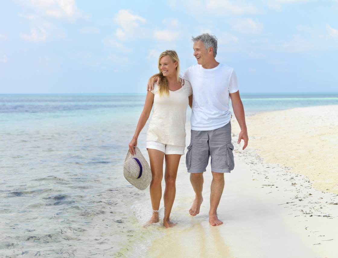 Beautiful mature couple walking along the beach